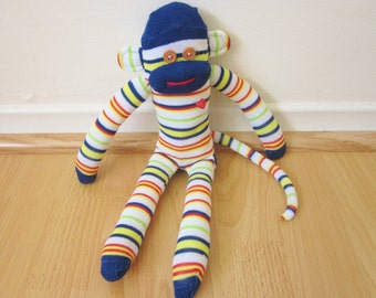 Blue and white striped sock monkey doll with red and yellow accents and red heart