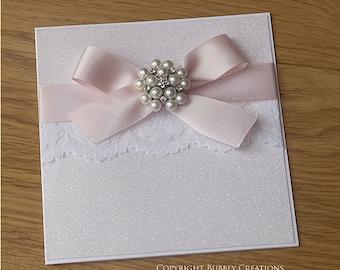 White Glitter wedding invitation with lace, satin ribbon bow and pearl embellishment. Sparkly, glitzy and elegant wedding invite - SAMPLE
