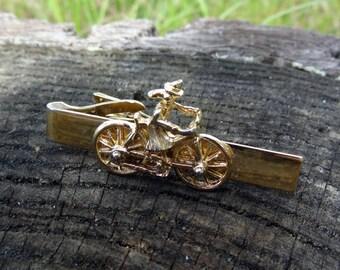 Gold tone tie clip, witch in a bike