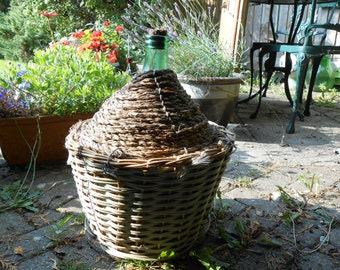 Glass demijohn, italian damigiana, 15 litre green glass bottle in basket with wooden base.