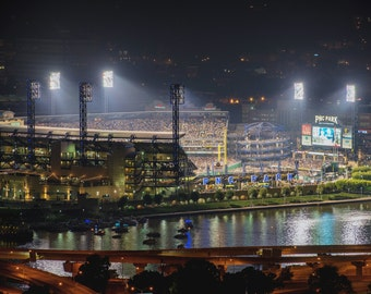 PNC Park is lit up at night during a Pittsburgh Pirates game - Metal Print