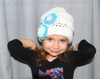 White knitted hat with aqua color flowers. For ages 2-3