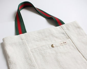 White tote bag with green and red handle