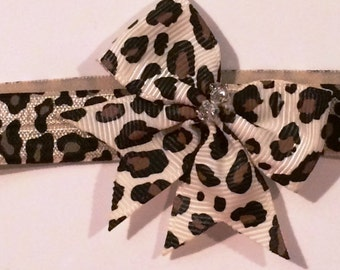 Leopard Print Headband accented with a simple Leopard bow accented with 2 crystals.