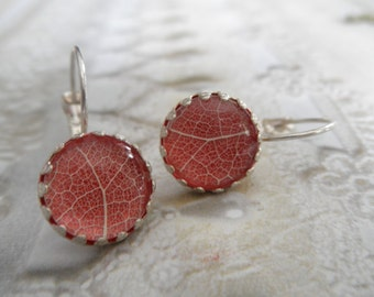 White Skeleton Leaf Crown Leverback Earrings Beneath Glass Atop Vivid Red Background-Gifts Under 30-Symbolizes Tranquility, Serenity