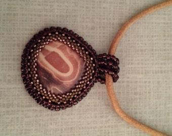 Bead embroidered jasper pendant on leather