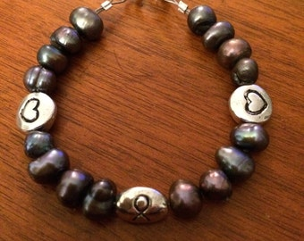 Purple freshwater pearl with cancer ribbon charm