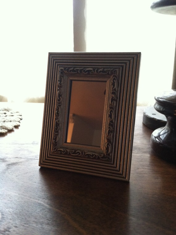 Pewter colored small decorative framed mirror display on a for Small decorative wall mirrors