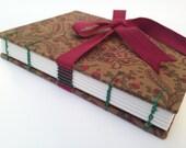 Cuaderno cosido a mano con hilo de lino encerado y forrado con tela 100% algodón. Encuadernado cosido copto y cierre con lazo.