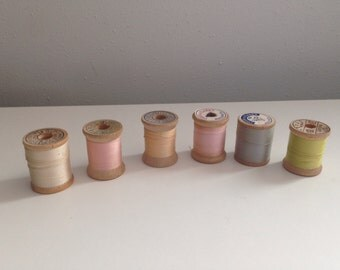 Vintage sewing thread lot of 6 wooden spools in pastel colors cream, pink, peach, grey and green thread