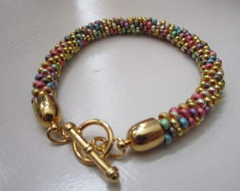 Multi colored kumihimo beaded bracelet with gold toggle clasp