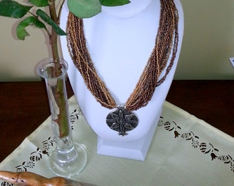 Vintage Ethnic multistring earth ton colors necklace with amazing Tibet silver pendant added.