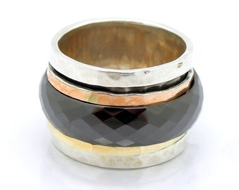 Wide spinner ring with black ceramic, yellow gold, rose gold and silver