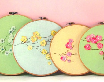 Hoop art of pink blossom branch with beaded embroidered flower centers on pale yellow fabric