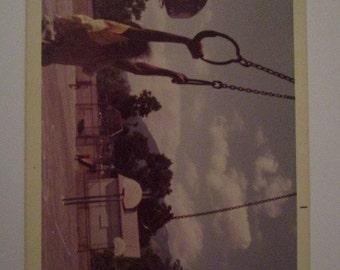 Vtg Color photo of little kid swinging near basketball court, around 1960s, 70s
