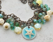 Starfish Ceramic Pendant Necklace A beach style necklace with floral-esque carved bone beads, golden paisley coins, & blue Czech glass beads
