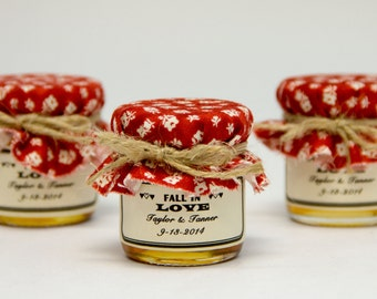 1 mini 2 oz. mason jar with red fabric and a twine bow with a label! Perfect for a barn, fall, winter wedding!