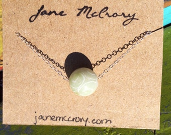 Carved green Jade necklace floating on sterling silver chain