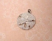 Sterling sand dollar charm and small silver tone cross charm