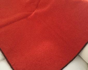 orange wool camp blanket with black stitching