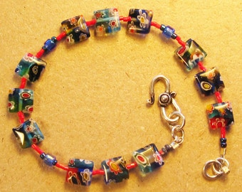 Delicate blue/black/red lampwork bead bracelet with red seedbeads and silver scroll fastener