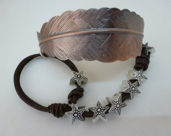Richly etched copper feather on deep brown Greek leather threaded by silver aluminum stars ties on with a casual knot  Floating Stars Bangle