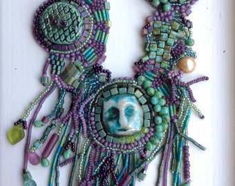 Raku face, bead embroidery and free form beaded necklace in greens and purples.