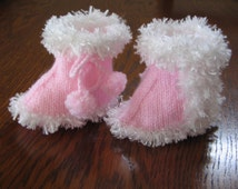 Hand knitted baby booties with fake fur trim.