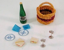Informal picnic woven round straw basket with handle, wine bottle, glasses, paper plates, napkins, wrapped sandwiches. Handmade in USA.