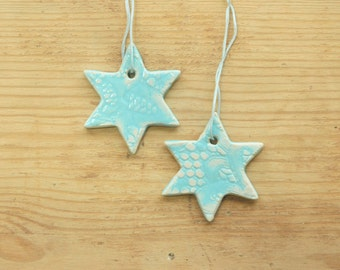 Set of two medium sized turquoise (on white clay) ceramic stars ornaments with lace pattern.