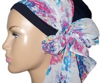 Navy blue turban adorned with a large veil band with fresh spring prints in pink, blue, yellow and white.