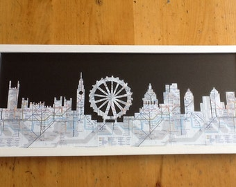 The London Skyline finely cut out of real London Underground tube maps on a black background, frame not included.