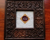 "Baha'i ""Greatest Name"" Embossed on a Red Rose Petal Set in a Square Carved Wooden Frame"