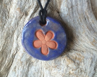 Diffuser necklace with flower emblem.