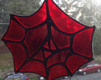 Stained glass spiderweb sun catcher with spider.