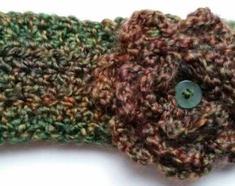 Size Adult. Multi colored greens headband with large green flower. Attached with 2 buttons in the back.