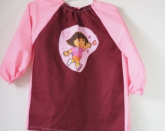 Child's art smock, age 3 to 4. Dora in dark pink and pink