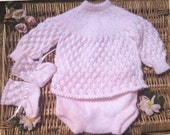 Newborn baby girl's pale pink hand knitted lacy pram outfit of lace dress, pants and bootees.
