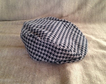 Tan and black houndstooth corduroy newsboy style cap.