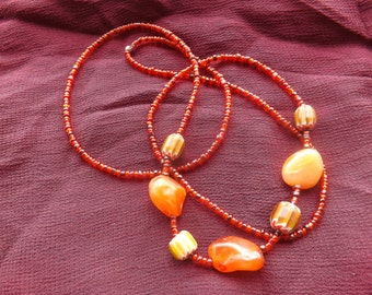 Long orangey red necklace.