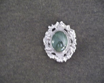 Beautiful deep swirl green colored African Praise cabochon set in white rhodium plated brooch setting.   Free shipping