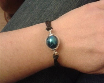 Bracelet with glass globe filled with sparkling blue sequins.