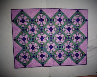 Quilt made with Batiks -  greens, pinks and purples.  Technique - paper pieced.