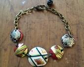 Red, gold, and black vintage tin bracelet