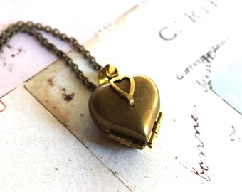 heart locket necklace. raw brass heart with 4 photo slots in the locket