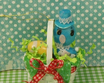Retro vintage Easter basket with blue bird yellow egg and red bow spring decor