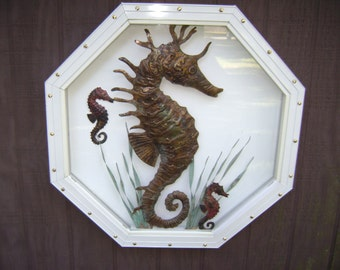 Handhammered sea horses in a frame.