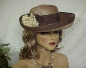 Linda --Pretty brown faux straw hat with darker brown grosgrain brim edge and ribbon-side flowers- fits 22 inches.