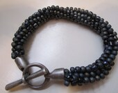 Gray and black kumihimo beaded braided bracelet with antique silver toggle clasp