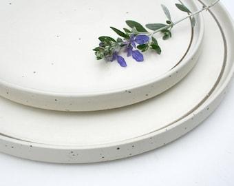 Two Dansk plates in Bornholm pattern. Dinner, serving, modern, Scandinavian design, white, off white, ivory, speckled, simple, clean lines